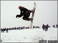 A snowboarder enjoys the winter weather at Hampstead heath