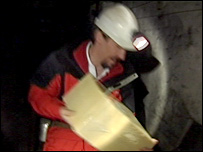 A Big Pit worker carries a 40kg block of cheddar cheese