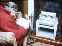 A female pensioner sitting in front of an electric heater at home