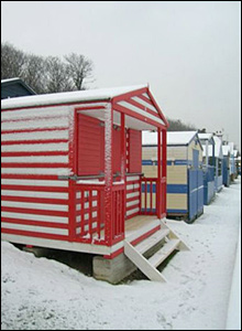 Snow on beach huts at Whitstable, Kent.