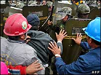 Bolivian workers try to stop riot police and soldiers bursting into metal foundry.