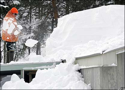 Bob Munger clears snow from the roof of his mother's house in Mexico, NY