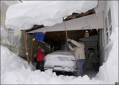 Residents of Oswego clear snow from their home