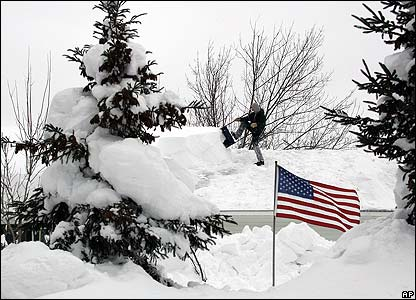 A US flag stands amid snow in front of a house in Mexico, NY