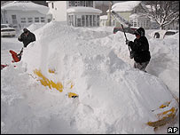 Residents dig their car out of the snow in Oswego, New York
