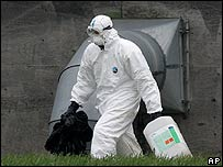 A worker in protective clothing performs a clean-up at a UK turkey farm