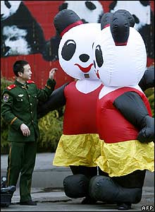 A Chinese paramilitary soldier plays with two air-inflated pandas