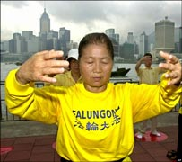 Falun Gong members meditate against the Hong Kong skyline