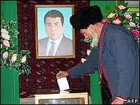 A man wearing national Turkmen clothes casts his ballot