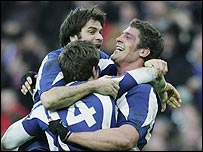 Vincent Clerc (number 14) celebrates with Christophe Dominici and Pascal Pape (R)