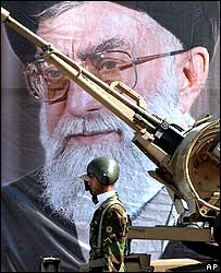 Iranian soldier in front of poster of Ayatollah Khamenei