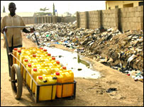 Man selling water, walking through rubbish heap