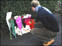 A neighbour looks at flowers outside the Gipton house