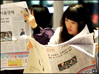 South Koreans read newspapers with details of the deal with North Korea