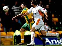 Norwich's Darren Huckerby (left) races away from Ian Evatt