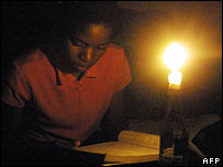 A Zimbabwe student reads by candlelight