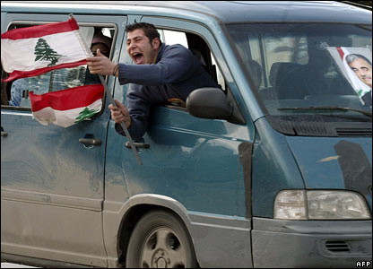 A Lebanese waves his country's flag.