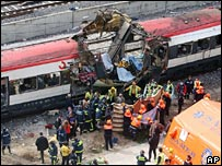 Rescue workers search one of the damaged passenger trains