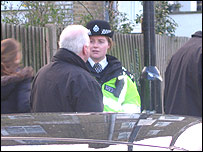 Photo of a man being spoken to by a police officer