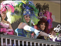Women throw beads to the crowd on Bourbon Street in the French Quarter of New Orleans on 16 Feb