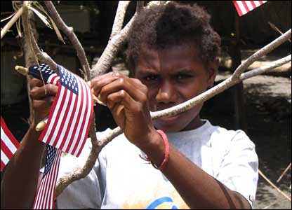 Boy ties US flags to a bush in Tanna