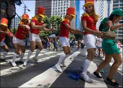 Men dressed as majorettes dance conga