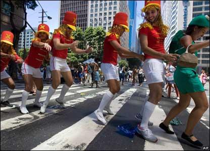 Men dressed as majorettes dance conga