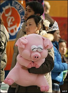 Girl holds stuffed pig at Ditan Park Temple Fair in Beijing, China