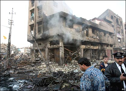 Iraqis stand by a building badly damaged in bomb blasts in Baghdad