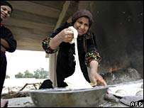 Poor Baghdad woman bakes bread under a bridge