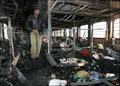 A policeman investigates the inside of one of the burned out train compartments