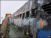 Police stand guard at the scene of the charred train