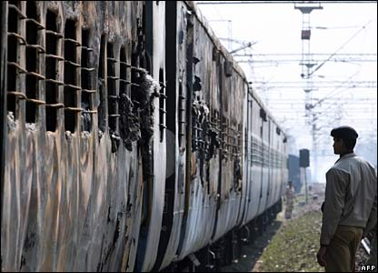Police stand guard at the scene of the burnt train