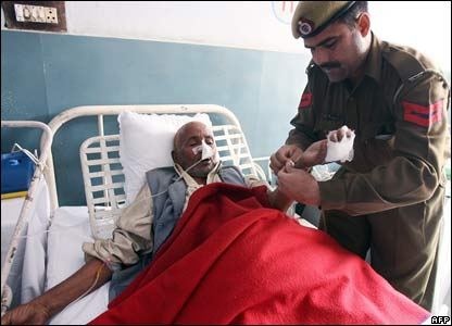 An Indian police personnel from Haryana helps Pakistani injured man Kamruddin, 60, from Multan, as he lies on a bed