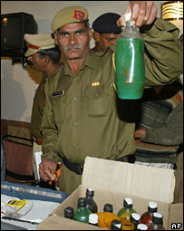 An Indian police officer shows bottles containing petrol and kerosene recovered from the train