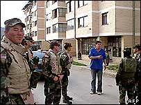 US soldiers talk to a civilian in Sonja Karadzic's apartment complex