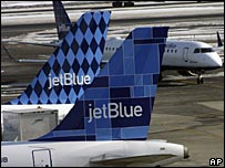 Tailfins of jetBlue aircraft on a snowy runway