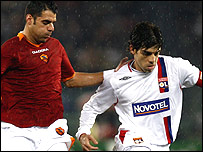 Lyon's Juninho [right] is challenged by Simone Perrota