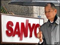 Man walking past Sanyo sign