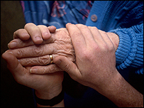 A carer holding an elderly person's hand