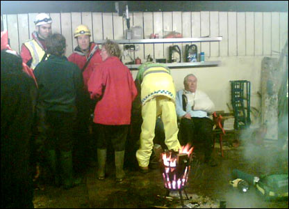 An injured passenger sits in front of a fire at a farm near the crash site (picture from Caroline Thomson)