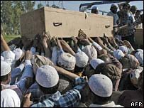 Mourners help to unload a coffin from a lorry in Mehrana, northern India