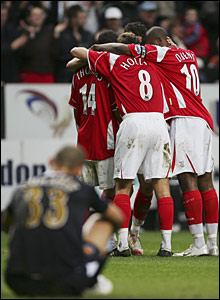 West Ham's Nigel Quashie sits dejected as Charlton celebrate Jermone Thomas's second goal