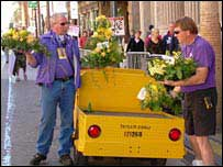People removing flowers from truck
