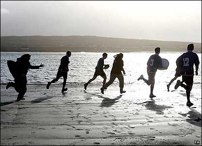 A nun chases the Inis Mor team along the beach