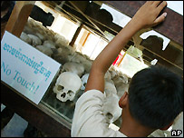 A Cambodian boy looks at a display of skulls at the Choeung Ek memorial