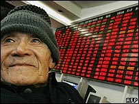 Chinese man stands next to electronic board showing share prices