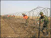 Barbed wire separating farm land from the village