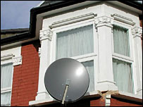 A satellite dish on the side of a house