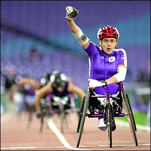 Tanni Grey-Thompson raises her fist in celebration after crossing the line in first place in the womens's 800m at the Paralympic Games in Sydney 2000